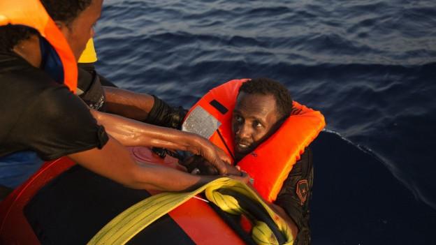 Ein Flüchtling mit Schwimmweste wird aus dem Mittelmeer gerettet.