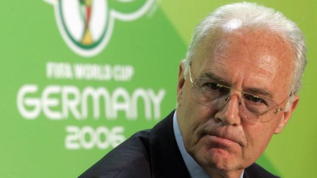Beckenbauer vor einem Plakat der WM 2006 in Deutschland, weisse Haare und Brille (29. Juni 2006).