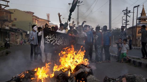 Demonstranten in Kaschmir vermummt auf der Strasse, vor ihnen brennt ein Feuer (6. August 2016).
