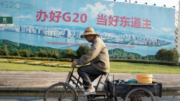"""Ein Mann fährt mit dem Velo an einem Propaganda-Plakat mit der Aufschrift """"G20 gut organisieren, ein guter Gastgeber sein"""" vorbei."""