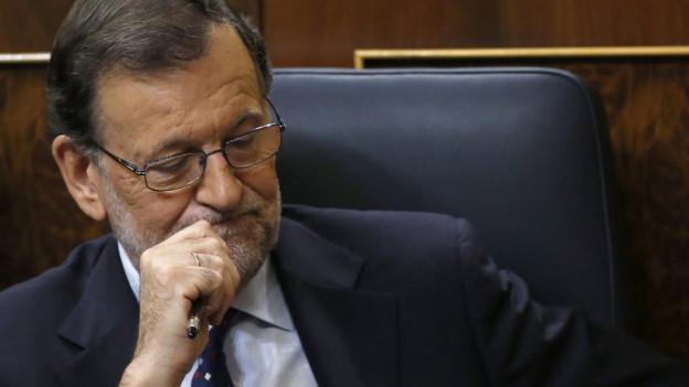 Manuel Rajoy sitzt im Parlamentssaal und macht ein nachdenkliches Gesicht.