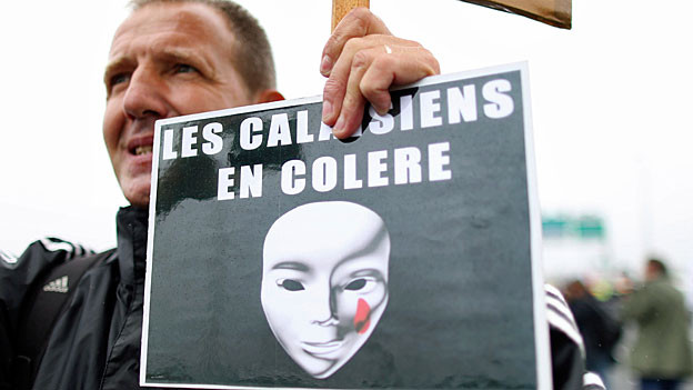Ein Mann aus Calais hält ein Plakat: «Les Calaisiens en Colère» steht in weissen Buchstaben auf schwarzem Grund.