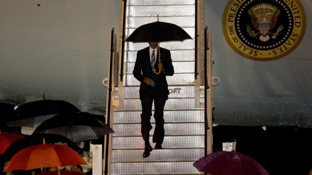 Obama steigt mit Regenschirm aus der Air Force One.