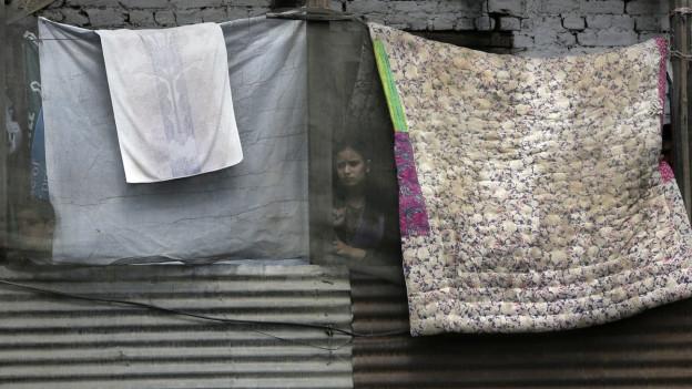 Eine junge Frau schaut zwischen grossen Tüchern hindurch, aus einem Fenster.