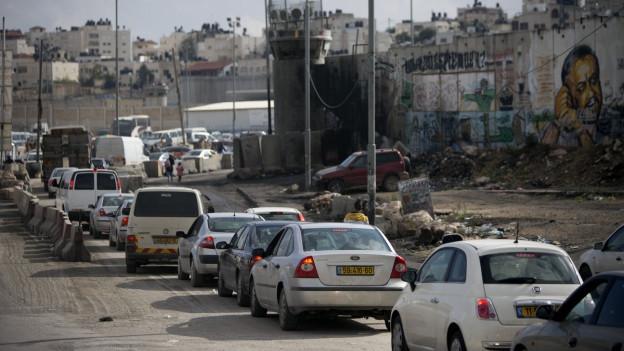Vor einem Checkpoint hat sich eine Autoschlange entlang einer Mauer gebildet.