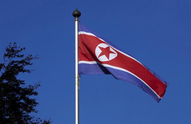 Eine nordkoreanische Flagge weht an einem Masten, im Hintergrund blauer Himmel.