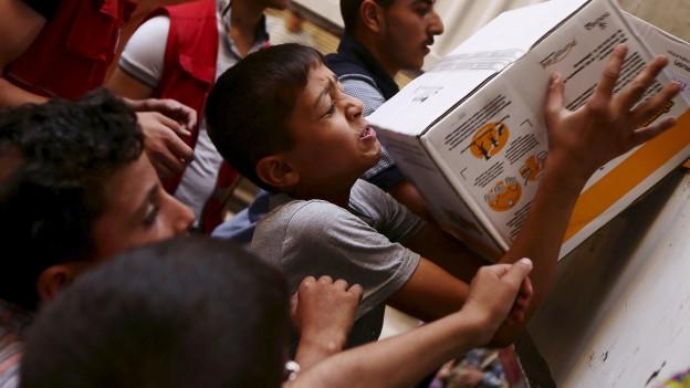 Zu sehen ist die Verteilung von Hilfsgütern des syrischen Halbmondes an die notleidende Bevölkerung.