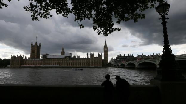 Zu sehen ist das britische Parlamentsgebäude, darüber dunkle Wolken.