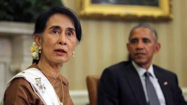 Das BIld zeigt im Vordergrund Aung San Suu Kyi und im Hintergrund Barack Obama.