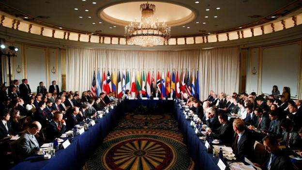 Ein UNO-Konferenzsaal mit vielen Flaggen - bereit für Gespräche über Flucht und Migration.
