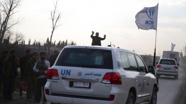 Ein Konvoi der UNO, der jubelnd empfangen wird.