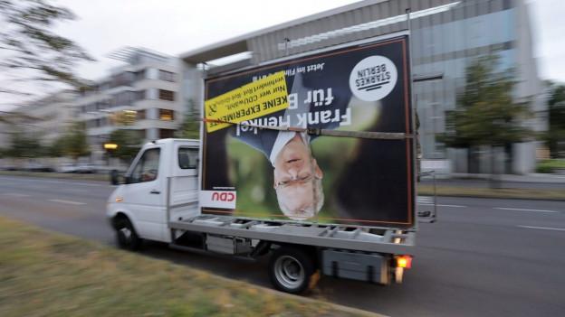 Ein Lastwagen mit CDU-Wahlplakat, das auf dem Kopf steht, fährt vorbei.