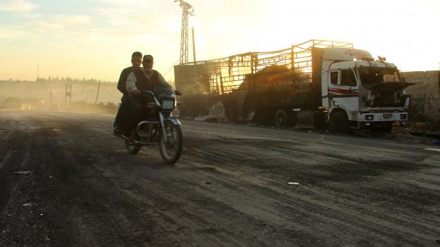 Zwei Männer fahren auf ihrem Motorrad an einem ausgebrannten LKW vorbei.