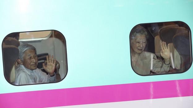 Das japanische Kaiserpaar winkt aus einem Zug.