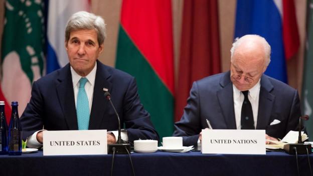 John Kerry und Staffan de Mistura sitzen hinter einem blauen Tisch und machen eine konsternierte Mine.