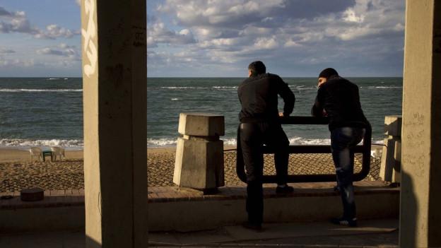 Zwei syrische Flüchtlinge stehen am Ufer in Alexandria (Ägypten) und schauen aufs Meer hinaus.
