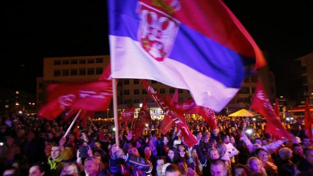 Menschen in Bosnien schwenken Fahnen während der Feierlichkeiten in der bosnischen Stadt Pale.