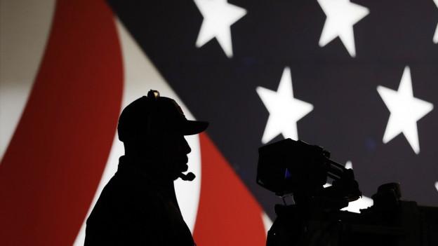 Das Bild zeigt die Silhouette eines Kameramannes vor einer USA-Fahne