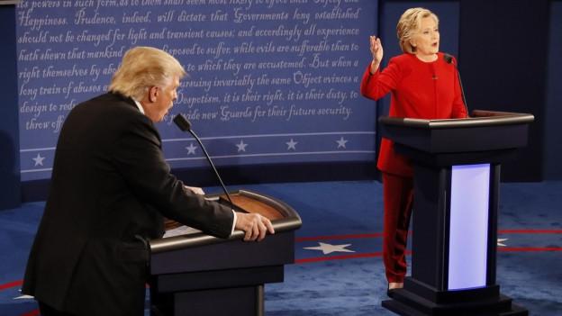 Hillary Clinton und Donald Trump stehen hinter ihrem jeweiligen Rednerpult und diskutieren.
