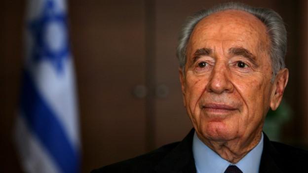 Shimon Peres mit der israelischen Flagge im Hintergrund.