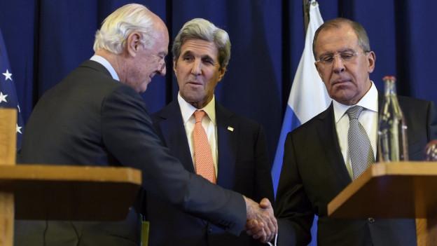 Der UN-Sondergesandte Staffan de Mistura schüttelt nach den Syrien-Gesprächen in Genf die Hand des russischen Aussenminister Sergei Lawrow, dazwischen steht US-Aussenminister John Kerry.