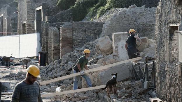 Arbeiten mit gelben Helmen arbeiten in Pompeji an einem eingstürzten Gebäude.