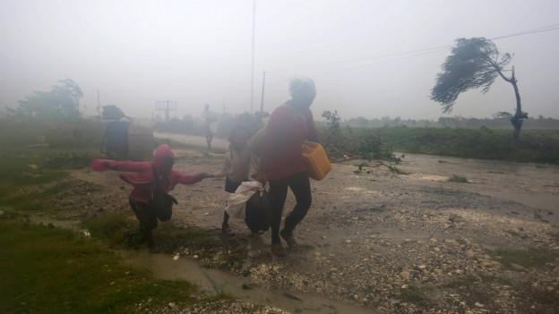 Eine Mutter kämpft sich mit ihren beiden Kindern durch den Sturm, der im Hintergrund Bäume umbiegt.