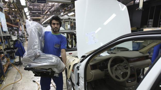 Ein iranischer Arbeiter baut einen Sitz in ein Fahrzeug ein.