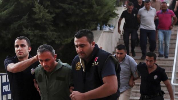 Polizisten führen Armeeangehörige ab.