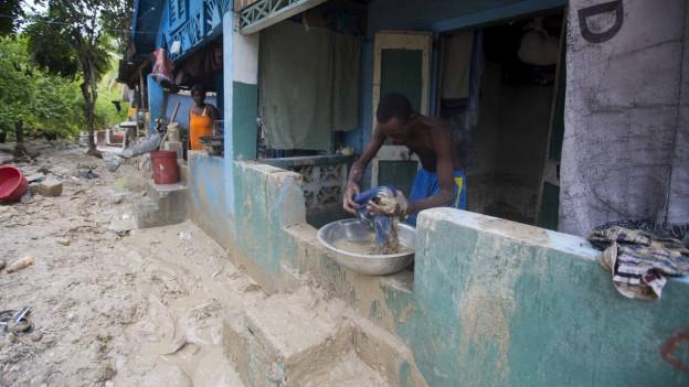 Ein Mann räumt Schlamm weg vor seinem Haus in Grand Goave in Haiti.