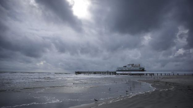 Der Daytona Beach in Florida, der Boardwalk im Hintergrund, graue Wolken am Himmel, es braucht sich was zusammen (6. Oktober 2016).