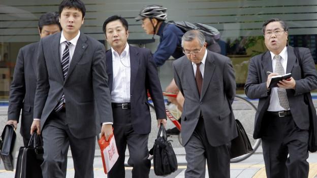 Japanische Geschäftsmänner überqueren in Tokyo eine Strasse.