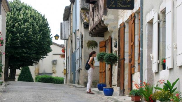 Einsame Touristin in einem verlassenen Dorf in Südwestfrankreich.