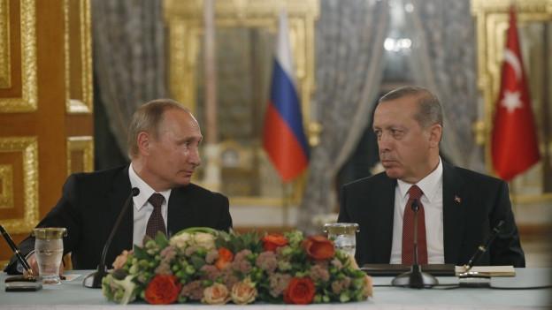 Russlands Präsident Putin und der türkische Präsident Erdogan sitzen nebeneinander an einem Tisch.