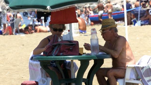 Zwei Rentner sitzen am Strand unter ihrem Sonnenschirm.