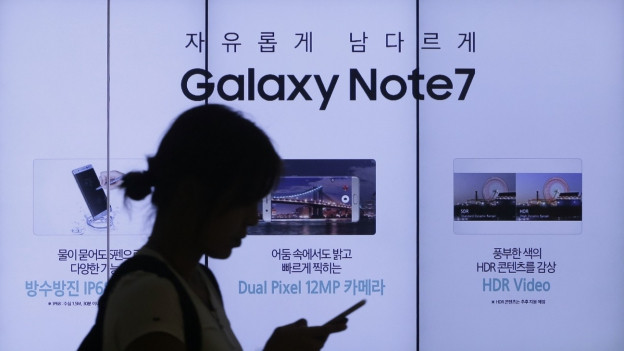Eine Frau mit Handy in der Hand läuft an einer Werbung für das Galaxy Note 7 vorbei.