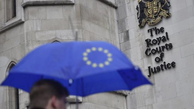 Ein Mann mit einem Regenschirm mit der EU-Flagge darauf geht vor dem High Court in London vorbei (13. Oktober 2016).