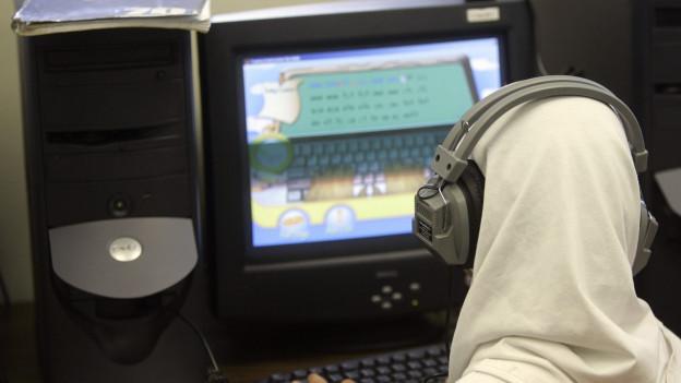 Eine muslimische Frau sitzt vor einem Computerbildschirm.