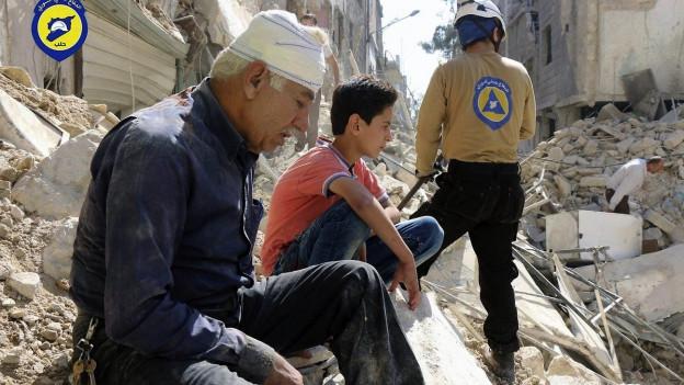Zwei Männer, einer mit Kopfverband, sitzen auf Trümmern in Aleppo, daneben ein Helfer mit Helm.