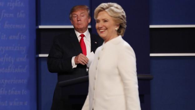Trump im Hintergrund, Clinton läuft lächelnd vorbei