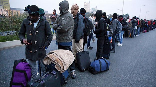 Flüchtlinge stehen Schlange mit ihren Reisetaschen.