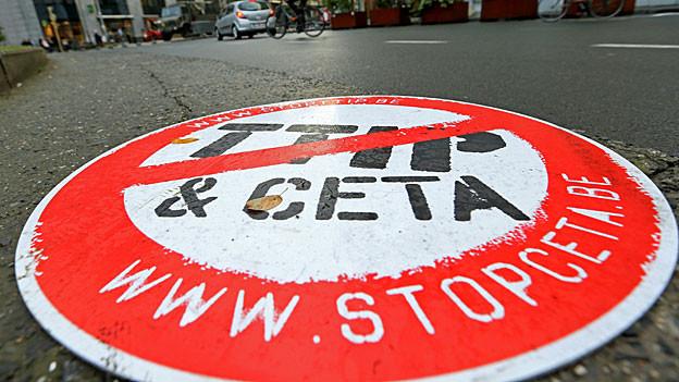 «Stop TTIP und CETA» steht auf einem runden Plakat vor dem EU-Sitz in Brüssel.