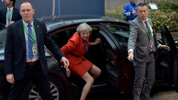 Die britische Premierministerin steigt aus einem schwarzen Auto aus. Links und rechts stehen Sicherheitsmänner.