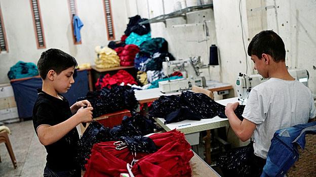 Zwei syrische Jungen arbeiten in einer Textilfabrik.