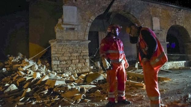 Zwei Helfer stehen vor einem eingestürzten Gebäude.