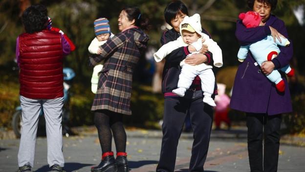 Vier chinesische Mütter, alle tragen je ein Kind auf dem Arm.
