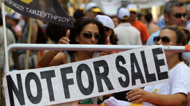 Eine Demonstration, im Vordergrund an einem Geländer ein Plakat mit der Aufschrift «Not for sale».