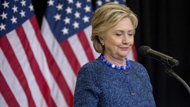 Auf dem Bild ist Hillary Clinton zu sehen an einer Medienkonferenz, an der die Präsidentschaftskandidatin Stellung nimmt zu den angekündigten Ermittlungen im Zusammenhang mit der E-Mail-Affäre.