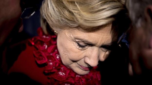 Porträt von Hillary Clinton, rotes Oberteil, sie steht in einer Menschenmenge, den Kopf und die Augen gesenkt (31. Oktober 2016).