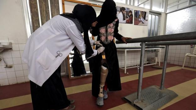 Eine verhüllte Frau bekommt von einer Therapeutin Hilfe mit ihrer Beinprothese.